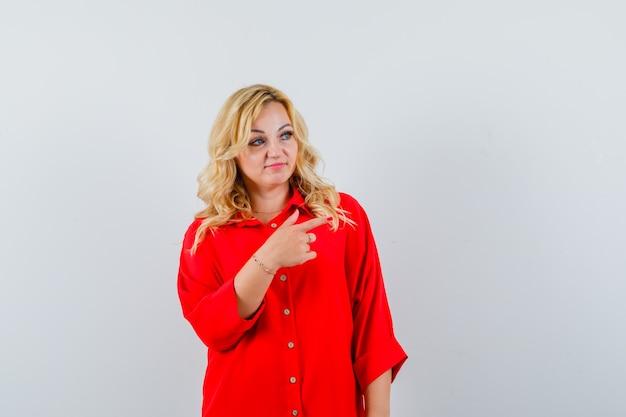 빨간 블라우스에 검지 손가락으로 오른쪽을 가리키고 예쁜, 전면보기를 찾고 금발 여자.