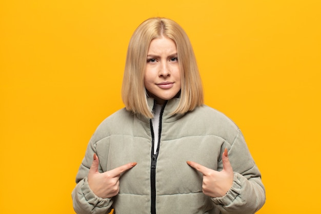 Blonde woman pointing to self with a confused and quizzical look, shocked and surprised to be chosen
