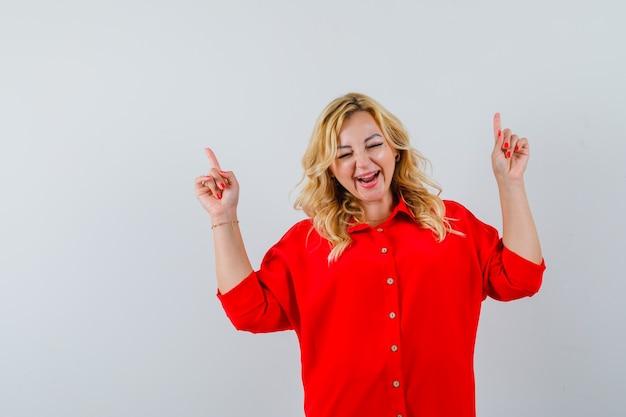 赤いブラウスで人差し指で上向きで幸せそうに見える金髪の女性。