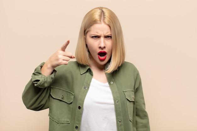 猛烈な狂気のボスのように見える怒っている攻撃的な表情で指しているブロンドの女性