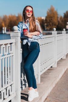 Blonde woman posing fashion next to a railing