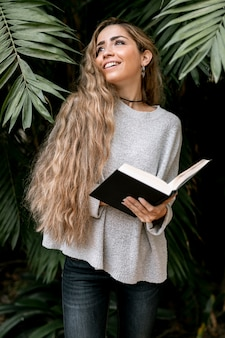 Blonde woman posing outside while holding a book