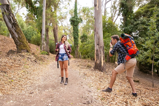Blonde woman posing for photo on road in forest. caucasian man holding camera and shooting on nature. two happy people trekking with backpacks. tourism, adventure and summer vacation concept