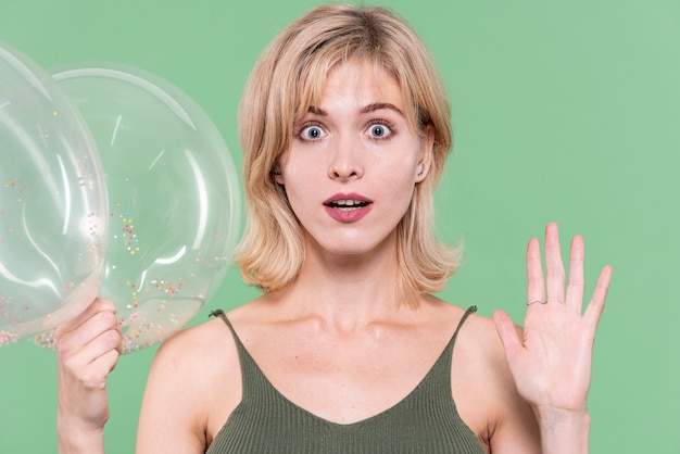 Blonde woman posing shocked and holding balloons