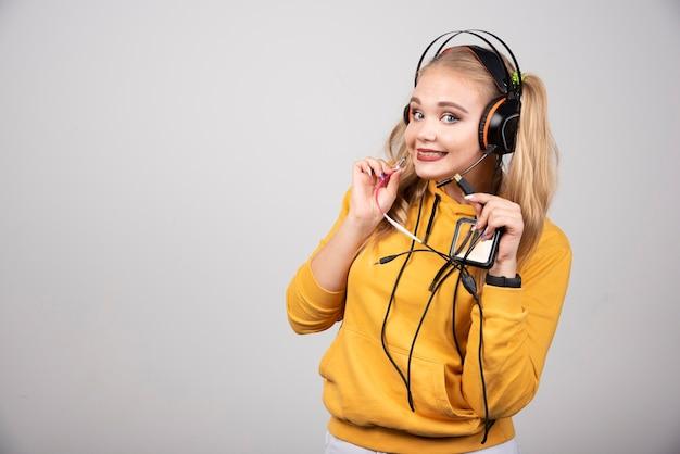 灰色の背景にヘッドフォンでポーズをとって金髪の女性。