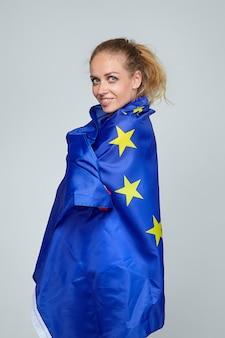 金髪の女性。欧州連合の旗でポーズ