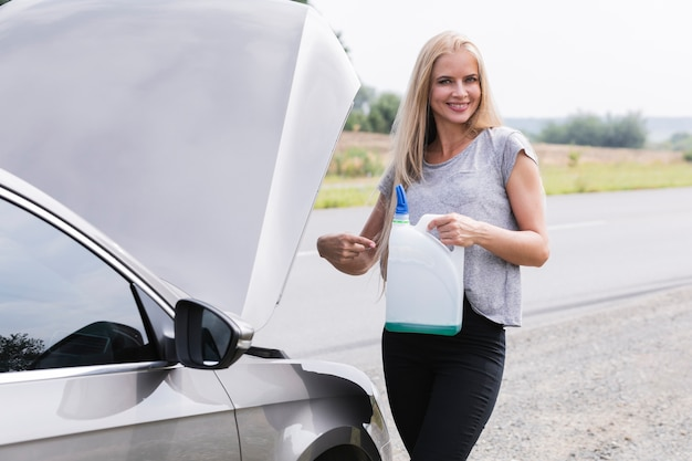 Blonde woman pouring windshield fluid