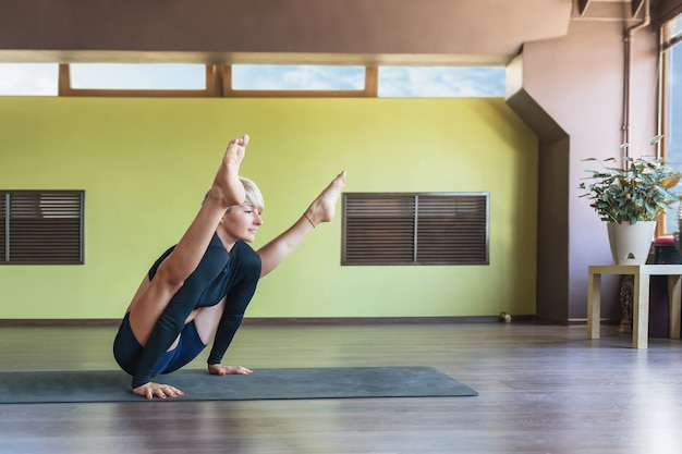 Blonde woman practicing yoga, performs in the gym exercise tittibhasana, firefly pose