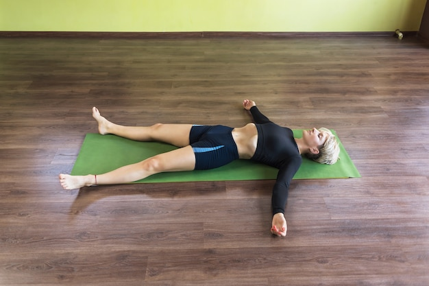 A blonde woman practicing yoga resting after a workout performs shavasana exercise with pranayama breathing practice