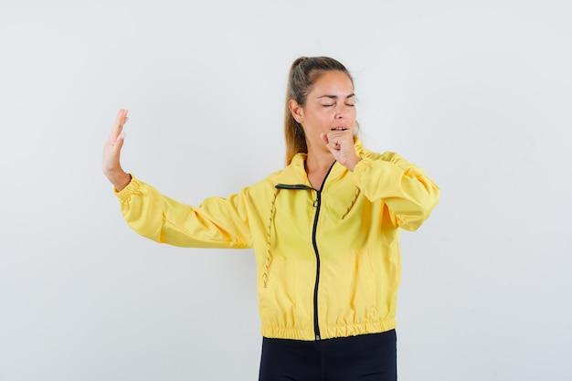黄色のボンバージャケットと黒のズボンで歌うふりをして面白がって見える金髪の女性 無料写真