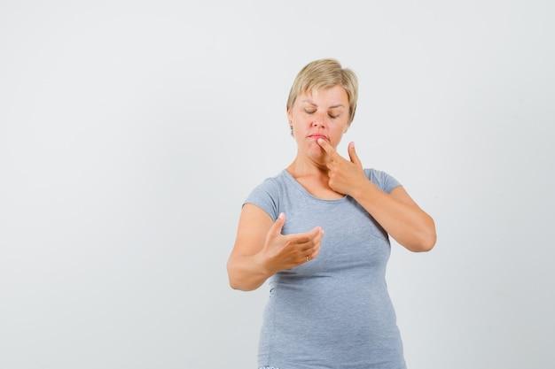 電話を見るふりをして、水色のtシャツを着て唇に指を置き、物思いにふける正面図を見る金髪の女性。