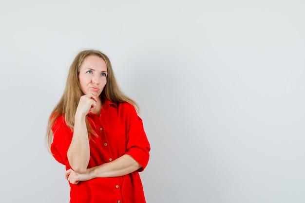 Donna bionda appoggiando il mento sulla mano in camicia rossa e guardando esitante,