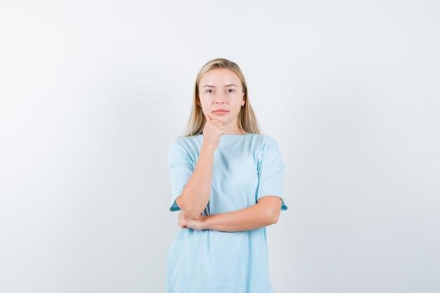 肘の下で手を握って、拳で顎を支えているブロンドの女性