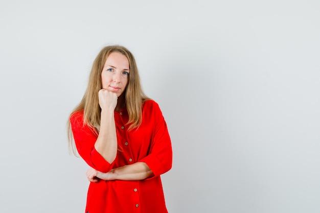 금발의여자가 빨간 셔츠에 주먹에 턱을지지 하 고 현명한 찾고.