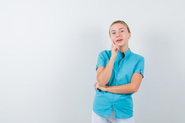 青いブラウスで手に顎を支え、陽気な孤立した探しているブロンドの女性