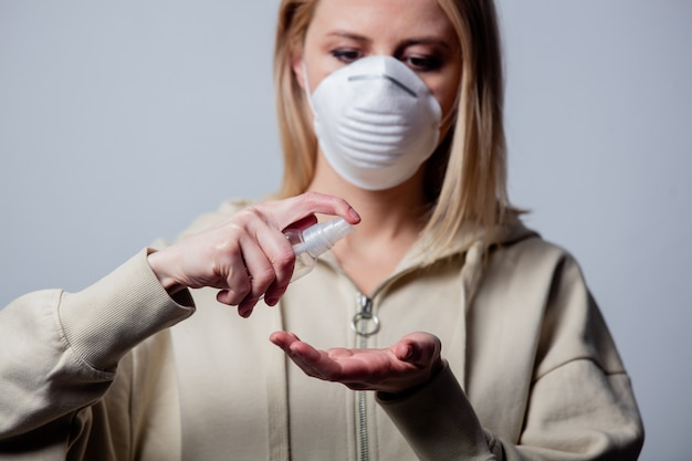 Blonde woman in protective mask  with disinfection gel