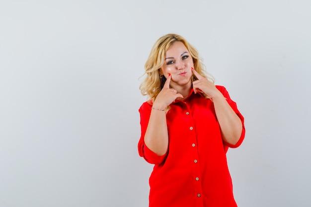 金髪の女性が頬を膨らませ、赤いブラウスの人差し指でそれを指して、きれいに見えます。正面図。