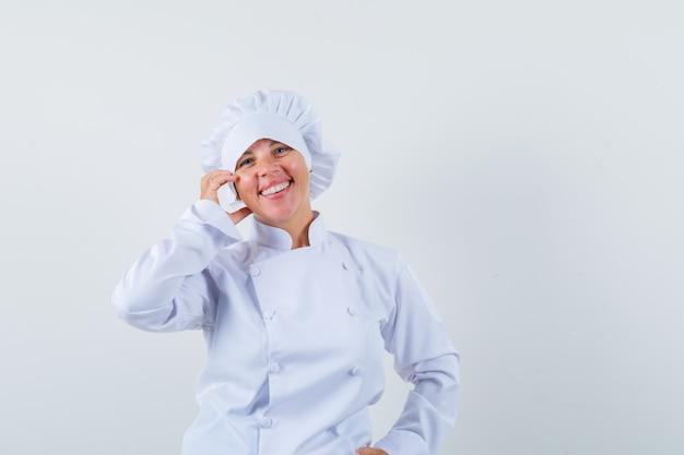 Donna bionda che mette la mano sulla guancia in uniforme bianca del cuoco e che sembra carina