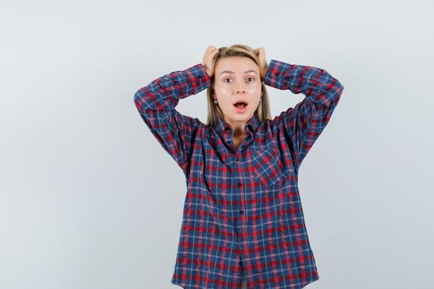 Donna bionda che mette le mani sulla testa, in piedi con la bocca aperta in camicia a quadri e guardando sorpreso. vista frontale.