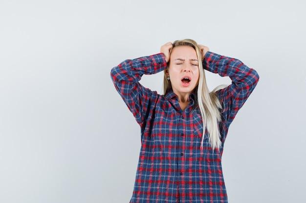 金髪の女性が頭に手を置き、チェックのシャツであくびをして眠そうに見えます。正面図。