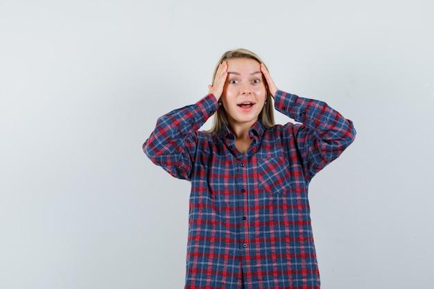 Блондинка положила руки на голову, стоя с открытым ртом в клетчатой рубашке и выглядела удивленной. передний план.
