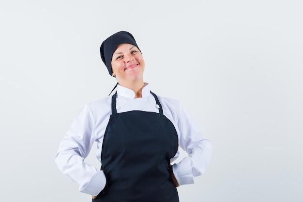 Блондинка женщина кладет руки на талию в черной форме повара и выглядит красиво, вид спереди.