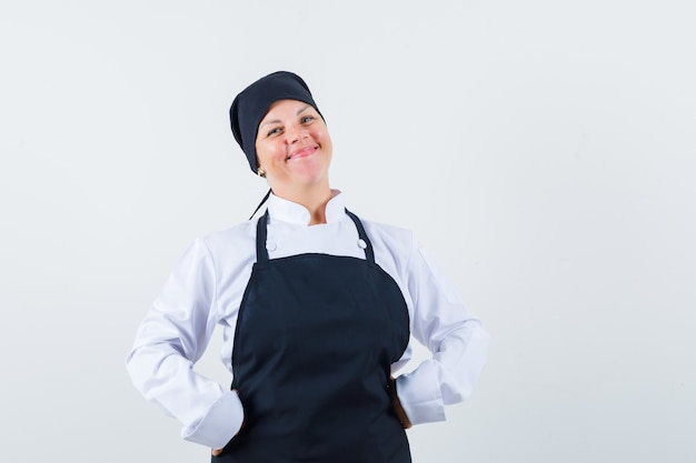 Blonde woman putting hands on waist in black cook uniform and looking pretty , front view.