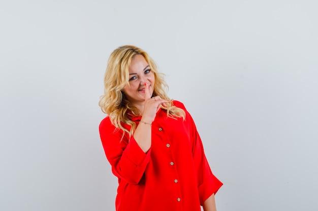 Donna bionda che mette il dito indice sulla bocca, mostrando il gesto di silenzio in camicetta rossa e guardando felice
