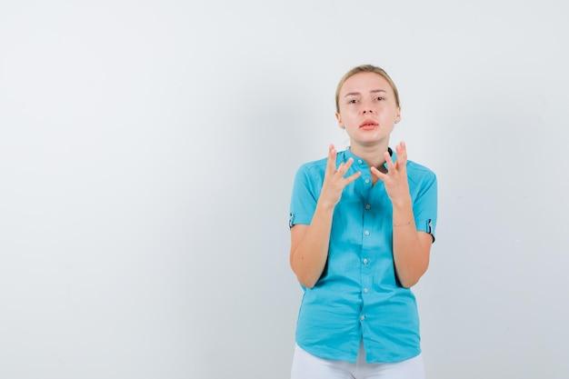 Donna bionda che alza le mani in camicetta blu e sembra indifesa isolata