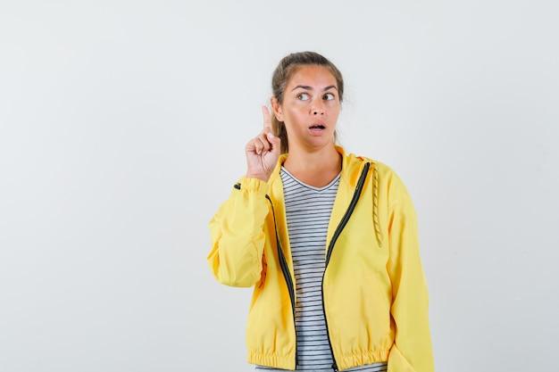 Donna bionda che alza il dito indice nel gesto di eureka e lo guarda in bomber giallo e camicia a righe e sembra serio