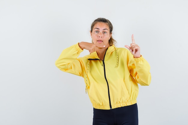 Blonde woman raising index finger in eureka gesture, pointing to it in yellow bomber jacket and black pants and looking happy