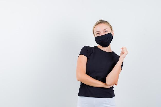 검은 티셔츠에 포즈를 취하는 동안 팔꿈치 아래 손을 잡고 한 팔을 들고 금발의 여자
