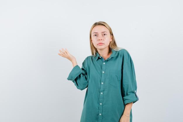 Блондинка поднимает руку в зеленой рубашке и смотрит задумчиво.