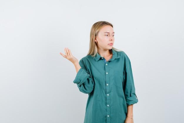 Donna bionda alzando il palmo della mano mentre guarda da parte in camicia verde e sembra pensierosa.