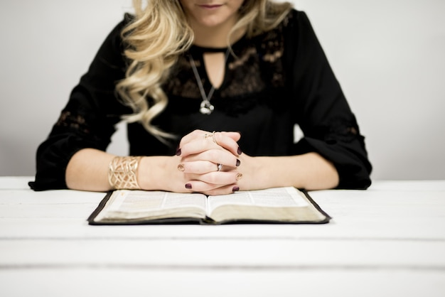Blonde woman reading a bible on the table