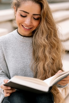 Blonde woman reading a book outside