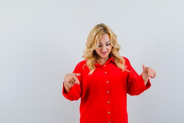 Donna bionda in camicetta rossa rivolta verso il basso con il dito indice e che sembra felice