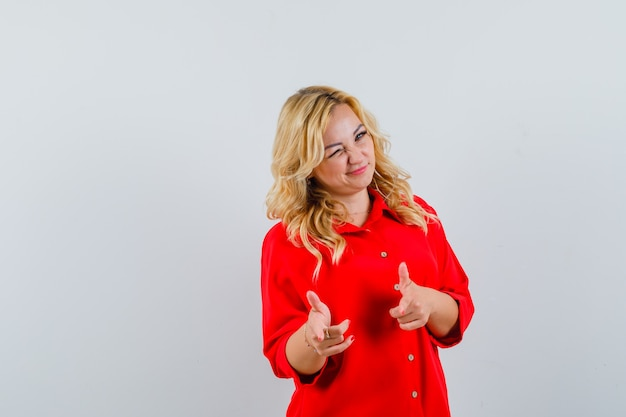 Donna bionda in camicetta rossa che punta il dito indice alla telecamera, ammiccando e guardando felice