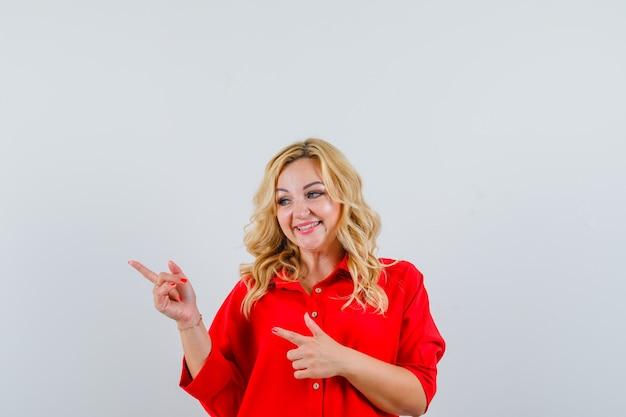Donna bionda in camicetta rossa che punta a sinistra con il dito indice e che sembra felice,
