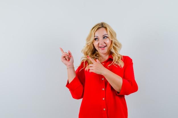 Donna bionda in camicetta rossa che punta in alto a sinistra con le dita indice e che sembra felice