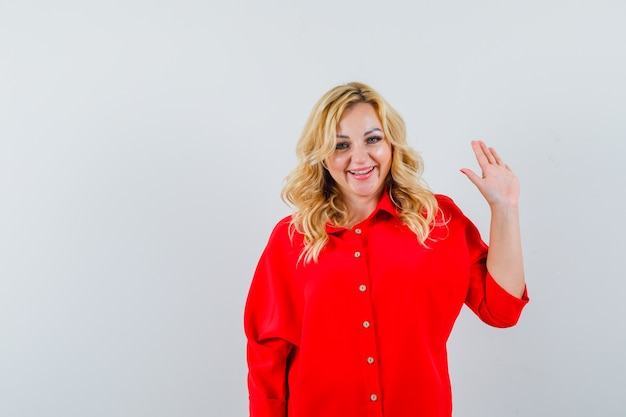 Blonde woman in red blouse raising hand as greeting someone and looking happy ,