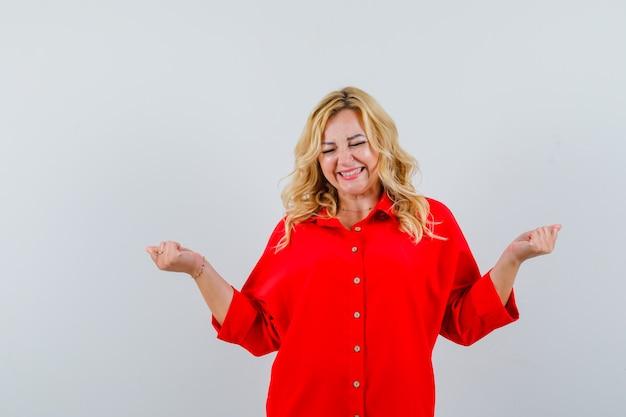 Donna bionda in camicetta rossa che mostra il gesto di successo, chiudendo gli occhi e guardando felice, vista frontale.