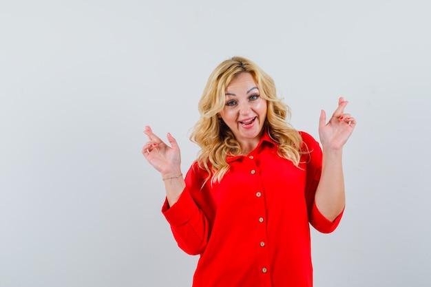 Donna bionda in camicetta rossa in piedi dita incrociate e guardando felice, vista frontale.