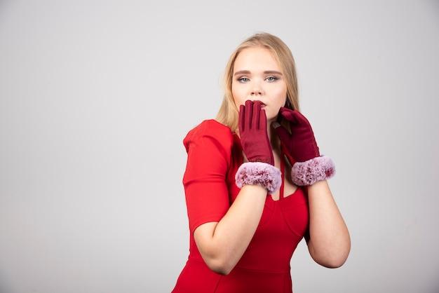 Donna bionda in abito da cocktail rosso che si sente sorpresa.
