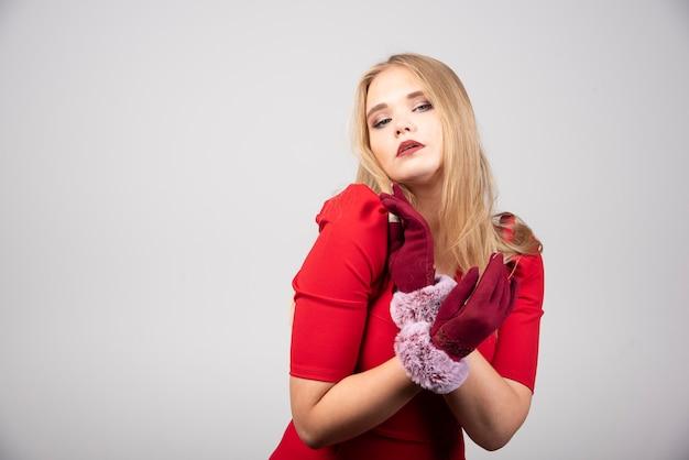 Donna bionda in abito da cocktail rosso che sembra alla moda.