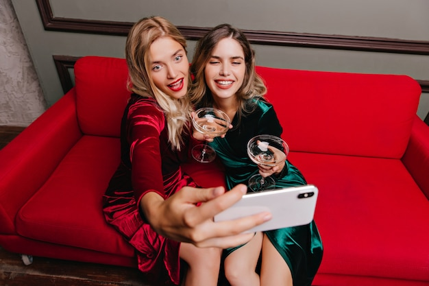 Blonde woman in red dress drinking chamagne with friend. lady in green attire posing on sofa.