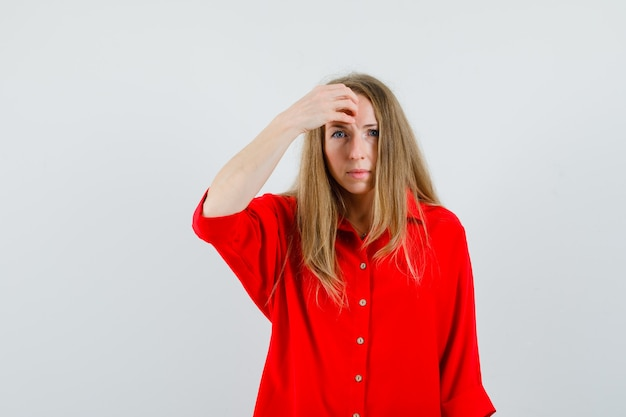 Blonde woman in red shirt holding hand on forehead and looking confused ,