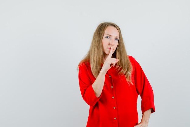 Donna bionda in camicia rossa che mostra gesto di silenzio e guardando attento,