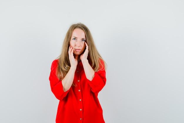 Donna bionda in camicia rossa che tocca la pelle del viso sulle guance e sembra sbalorditiva,