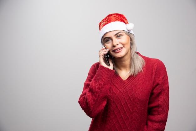 Donna bionda in maglione rosso che parla felicemente al cellulare.